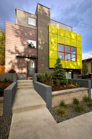 Modern Exterior of Home with Paint 1, Raised beds, Paint 2, Metal siding, Exterior brick, Pathway, Fence, picture window