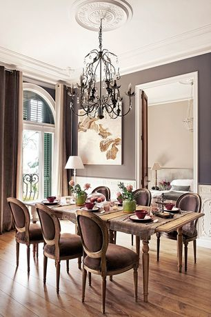 Traditional Dining Room with Chandelier, Standard height, Hardwood floors, Arched window, Crown molding, Wainscotting