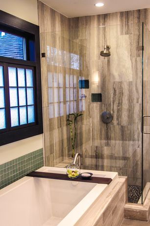 Asian Full Bathroom with frameless showerdoor, Daltile Stone Mosaics Black River Pebble Mosaic, Wall sconce, Rain shower