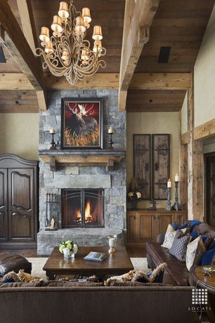 Traditional Great Room with stone fireplace, Cathedral ceiling, Columns, Chandelier, Exposed beam, Hardwood floors