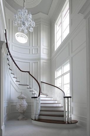Traditional Staircase with Raised paneling, round window, Hardwood floors, curved staircase, High ceiling, Paint, Chandelier