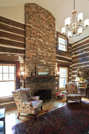 Rustic Living Room with stone fireplace, High ceiling, Floral Accent Chair, Area rug, Chandelier, Oriental rug