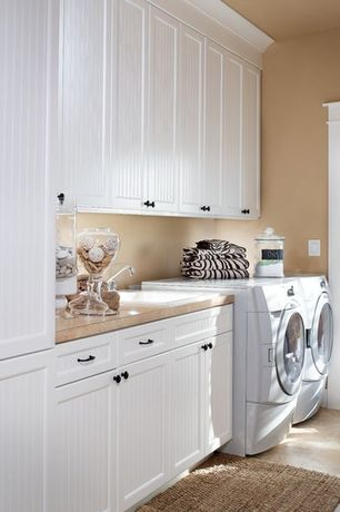 Cottage Laundry Room with Paint, travertine floors, French doors, Built-in bookshelf, Standard height, laundry sink