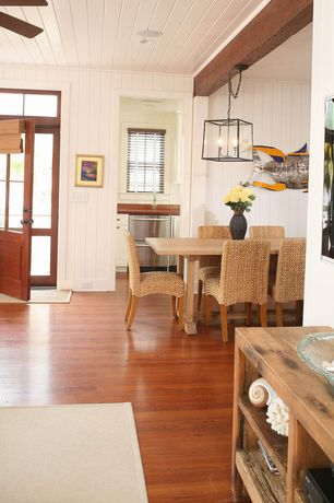 Cottage Dining Room with Glass panel door, Transom window, Chandelier, Built-in bookshelf, Ceiling fan, Exposed beam