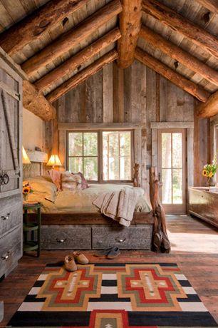 Rustic Master Bedroom with Built-in bookshelf, Hardwood floors, Glass panel door, High ceiling, Exposed beam