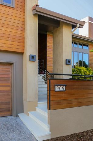 Contemporary Exterior of Home with Rain screen hardwood siding, Contemporary wood garage doors, Iron railings
