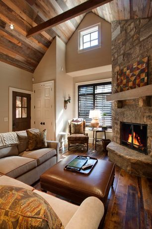 Country Living Room with Wood paneled ceiling, Exposed beam, Carlisle leather ottoman, stone fireplace, Hardwood floors