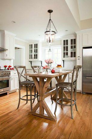 Traditional Dining Room with Built-in bookshelf, Hardwood floors, Chandelier, Crown molding, Casement, specialty door