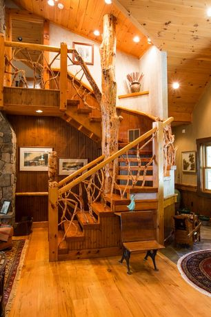 Rustic Staircase with can lights, curved staircase, High ceiling, Columns, Crown molding, Wainscotting, Hardwood floors
