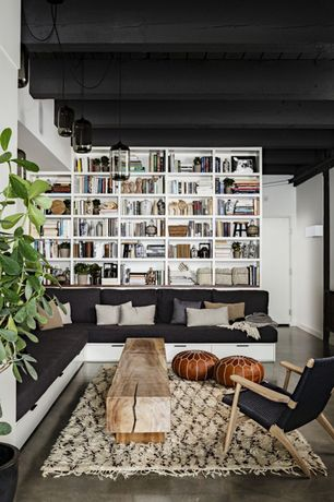Contemporary Living Room with Pendant light, High ceiling, Concrete floors, Brown moroccan leather pouf, Built-in bookshelf