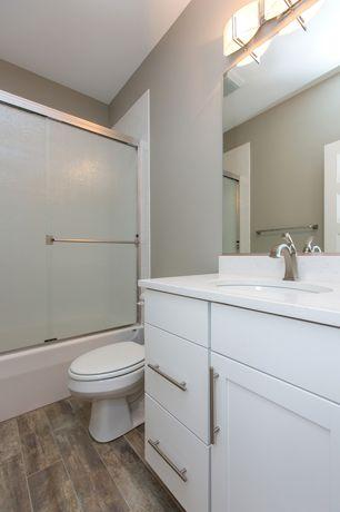 Modern Full Bathroom with Corian counters, European Cabinets, Hardwood floors, tiled wall showerbath, Flat panel cabinets