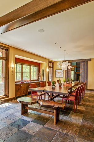 Rustic Dining Room with specialty door, Chandelier, Wall sconce, Custom live edge dining table, slate floors