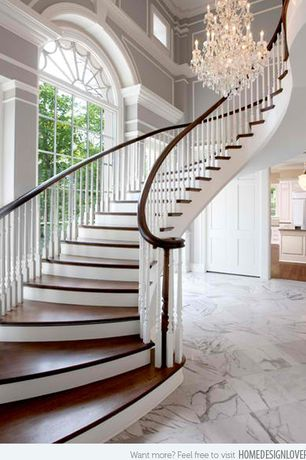 Traditional Staircase with curved staircase, High ceiling, six panel door, Chandelier, Arched window, Hardwood floors