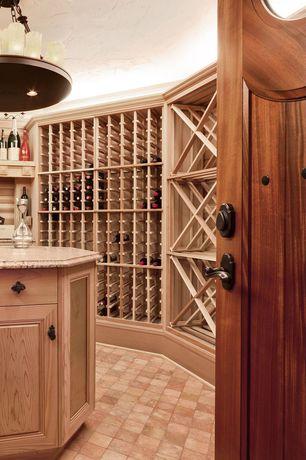 Mediterranean Wine Cellar with Built-in bookshelf, Glass panel door, Brick floors, Chandelier