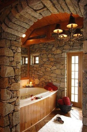 Rustic Master Bathroom with Frameless wall mirror, French doors, Stacked stone wall, Hardwood floors, Natural wood framing