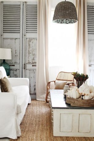 Eclectic Living Room with Built-in bookshelf, Salvaged shutter doors, Rattan lounge chair, Cabrillo pendant - natural, Carpet