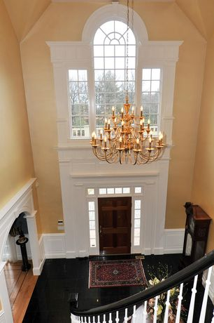 Traditional Entryway with Transom window, Cathedral ceiling, Paint, Arched window, six panel door, Chandelier, Wainscotting