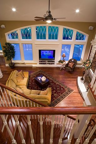 Traditional Living Room with Ceiling fan, flush light, High ceiling, Hardwood floors, Built-in bookshelf
