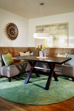 Contemporary Dining Room with Round area rug, Hardwood floors, L-shaped button tufted banquette, Pendant light