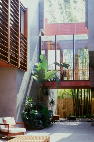 Asian Patio with Fence, picture window, exterior stone floors