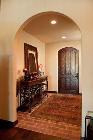 Mediterranean Entryway with Simple rugged round top exterior door in rustic hardwood with v-groove panels, Brick floors