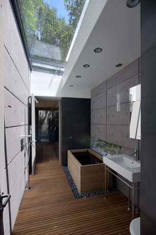 Contemporary Master Bathroom with Recessed ceiling lights, Concrete wall, Hardwood floors, Handheld showerhead, Console sink