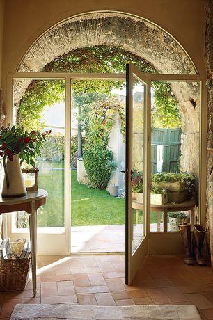 Cottage Entryway with Emporda, spain, SOCKER?RT Vase, French doors, Gustav Half Moon Table, terracotta tile floors