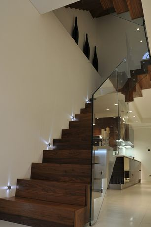 Contemporary Staircase with Wall sconce, High ceiling, Hardwood floors, curved staircase