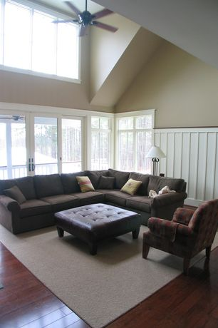 Traditional Living Room with Clerestory window, Leather ottoman, Wainscotting, Ceiling fan, Hardwood floors, French doors