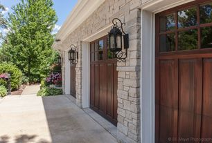 Traditional Garage with Lantern-style sconce, Natural stone exterior, Wrought iron wall sconce, Carriage house garage doors
