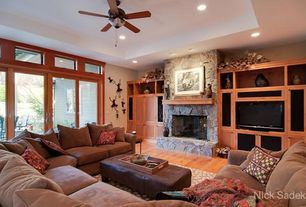 Country Living Room with Transom window, Laminate floors, High ceiling, French doors, Built-in bookshelf, stone fireplace