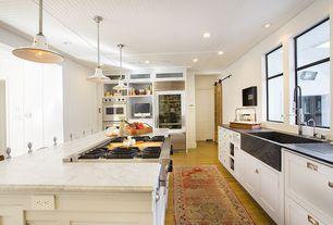 Modern Kitchen with Custom brazillian night soapstone farmhouse sink, Kitchen island, Pendant light, Glass panel, can lights