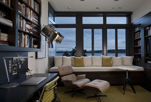 Contemporary Home Office with Built-in bookshelf, Carpet, Herman miller eames chair and ottoman