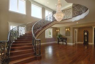Traditional Staircase with Hardwood floors, Cathedral ceiling, curved staircase, Chandelier, Casement, Crown molding, Loft