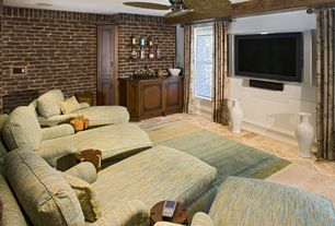 Traditional Home Theater with Chaise lounge, limestone floors, Ceiling fan, Wall mounted tv, Area rug, Interior brick wall