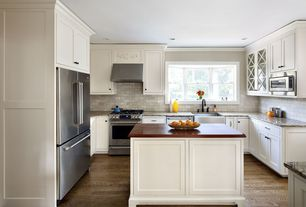 Traditional Kitchen with Crown molding, Shaker style cabinetry, Wood counters, Limestone Tile, Kitchen island, Glass panel