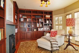 Traditional Home Office with flush light, metal fireplace, Casement, Hardwood floors, Standard height, Built-in bookshelf