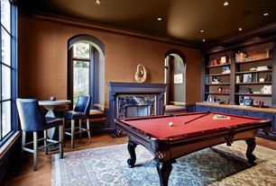 Traditional Game Room with Built-in bookshelf, Arched window, Crown molding, Window seat, Hardwood floors, High ceiling