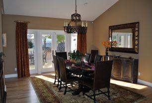 Mediterranean Dining Room with French doors, Chandelier, High ceiling, Hardwood floors