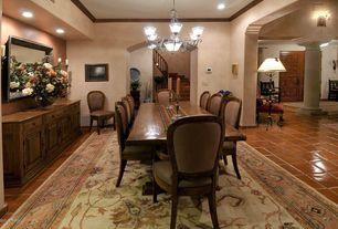 Mediterranean Dining Room with Chandelier, terracotta tile floors, Standard height, Built-in bookshelf, Crown molding, Carpet