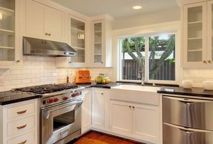 Traditional Kitchen with Subway tile backsplash, Stainless steel appliances, Flat panel cabinets, Glass door cabinets