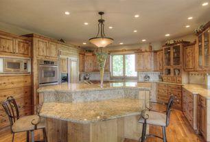 Mediterranean Kitchen with Hardwood floors, MS International  Golden Riviera Granite, Glass panel, Pendant light, U-shaped