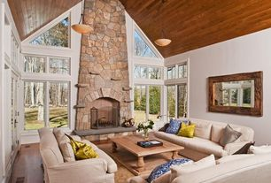 Rustic Living Room with French doors, Pendant light, High ceiling, metal fireplace, stone fireplace, Hardwood floors