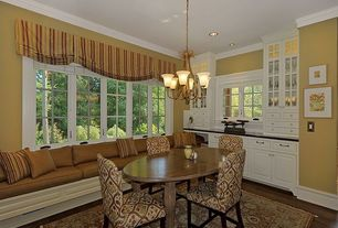 Traditional Dining Room with Crown molding, Casement, Standard height, can lights, Chandelier, Hardwood floors, Window seat