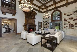 Traditional Living Room with French doors, stone fireplace, Chandelier, Built-in bookshelf, Exposed beam, Loft, Arched window