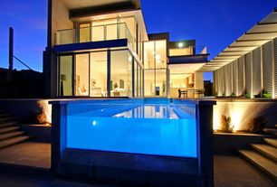 Modern Swimming Pool with Exterior accent lighting, Knoll barcelona chair, exterior stone floors, Pathway, Window wall