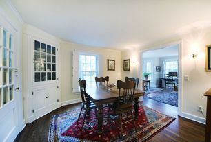 Traditional Dining Room with Wall sconce, Built-in bookshelf, double-hung window, Glass panel door, Hardwood floors