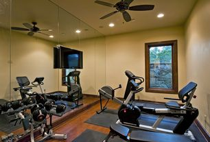 Contemporary Home Gym with Supermat 11gs tread mat, Hardwood floors, Kettler(r) favorite rowing machine, Ceiling fan