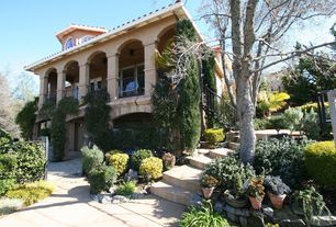 Mediterranean Patio with Exterior archway, Ivy, Exterior fan, Flagstone step, Covered balcony, Iron fence, Box hedge