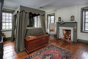 Traditional Master Bedroom with Paint 1, Belfort wingback upholstered armchair, Paint 2, Cement fireplace, Hardwood floors